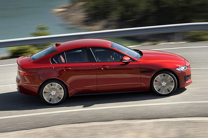 Side view of red Jaguar XE, driving on-road