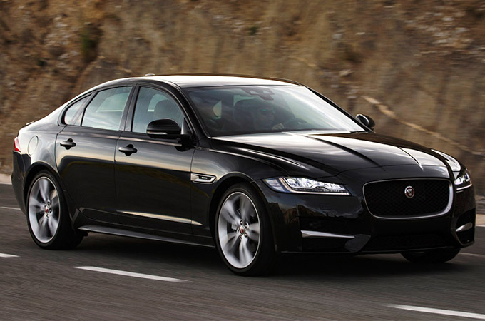 Side-front view of black Jaguar XF R-Sport, driving on-road