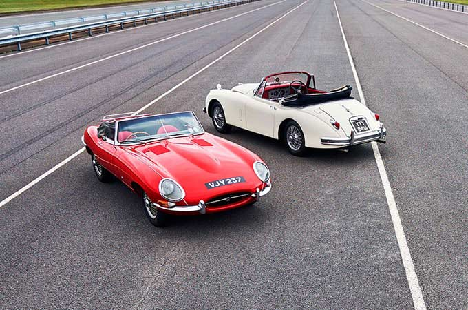 Two Jaguar Classics are parked next to each other, on-track