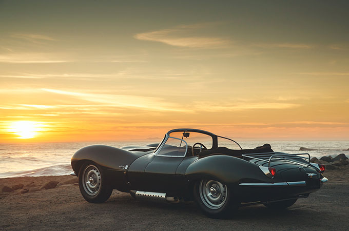 The Jaguar XKSS, parked on the beach, looks over the sea at sunset