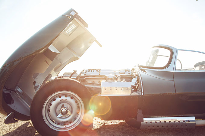 The sun beams down on the Jaguar XKSS, which has the bonnet lifted