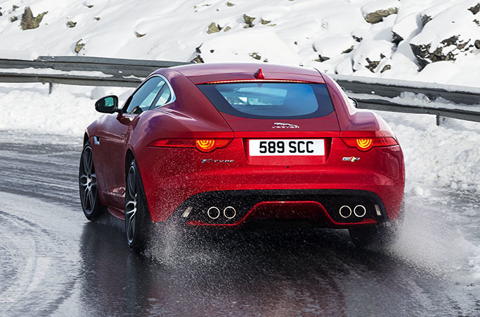 A Red Jaguar Driving On A Wet Road