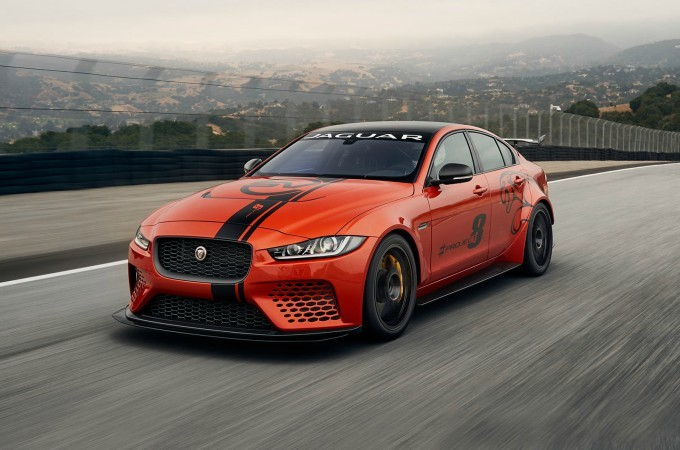 An Orange Project 8 Jaguar XE Driving On A Road.