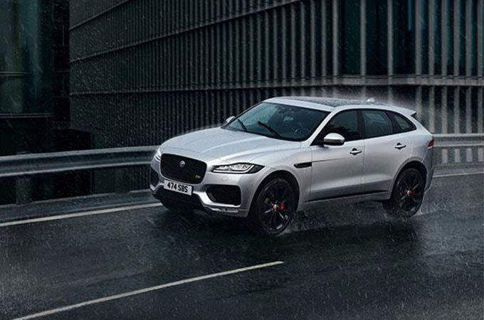 A Silver Jaguar F-PACE Driving In The Rain.