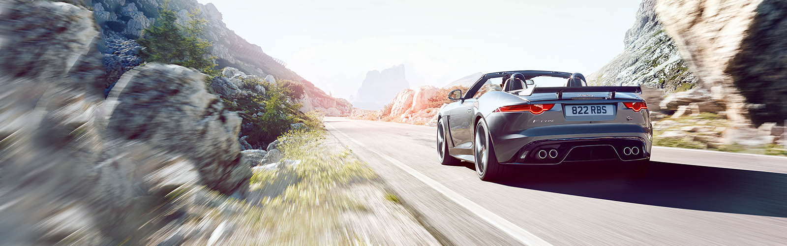 A Grey Jaguar F-Type Convertible Driving On A Road.