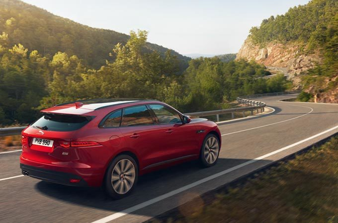 A Red Jaguar F-PACe Driving Along Road