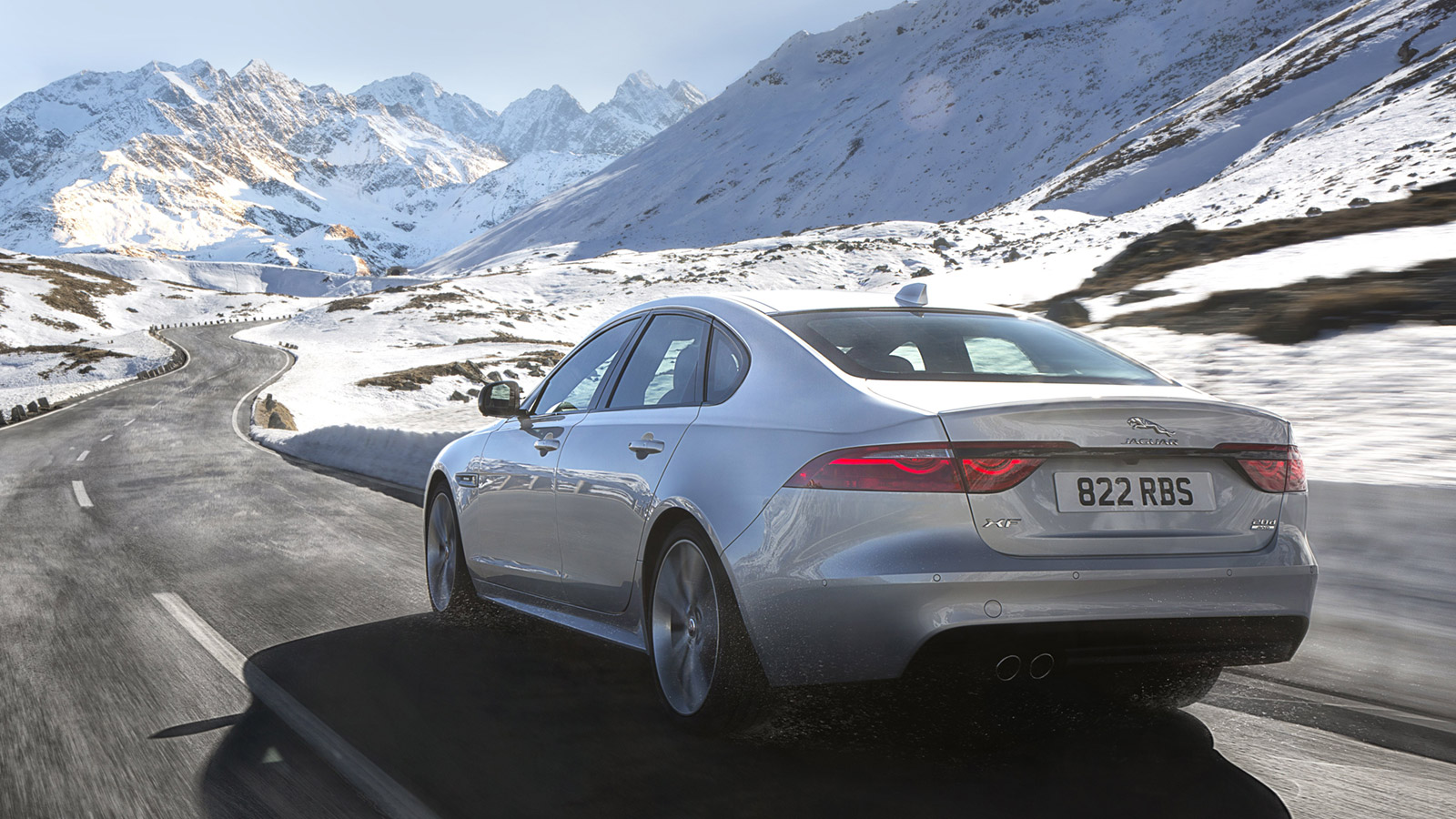 Rear view of Jaguar XF R-Sport, driving through snowy mountains