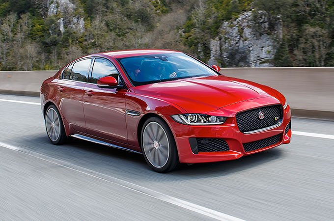 Red Jaguar XE Driving On A Road