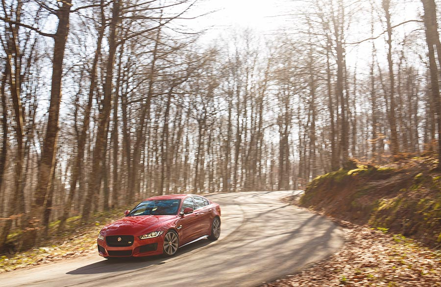 Red Jaguar Driving On A Road Through Some Trees