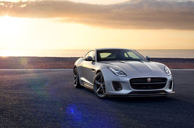 Front view of a silver Jaguar at sunset