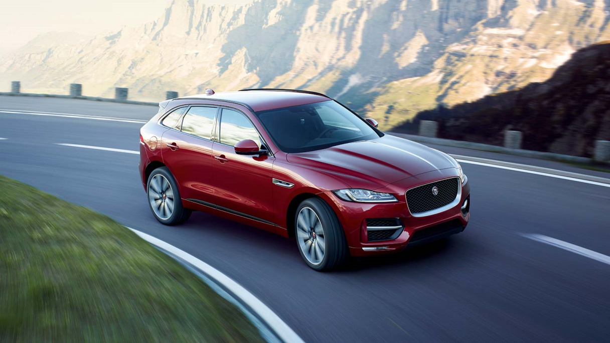 A Red Jaguar F-PACE Driving Near Some Mountains.