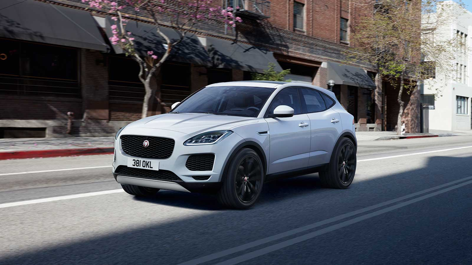 A White Jaguar E-PACE Driving In The Street.