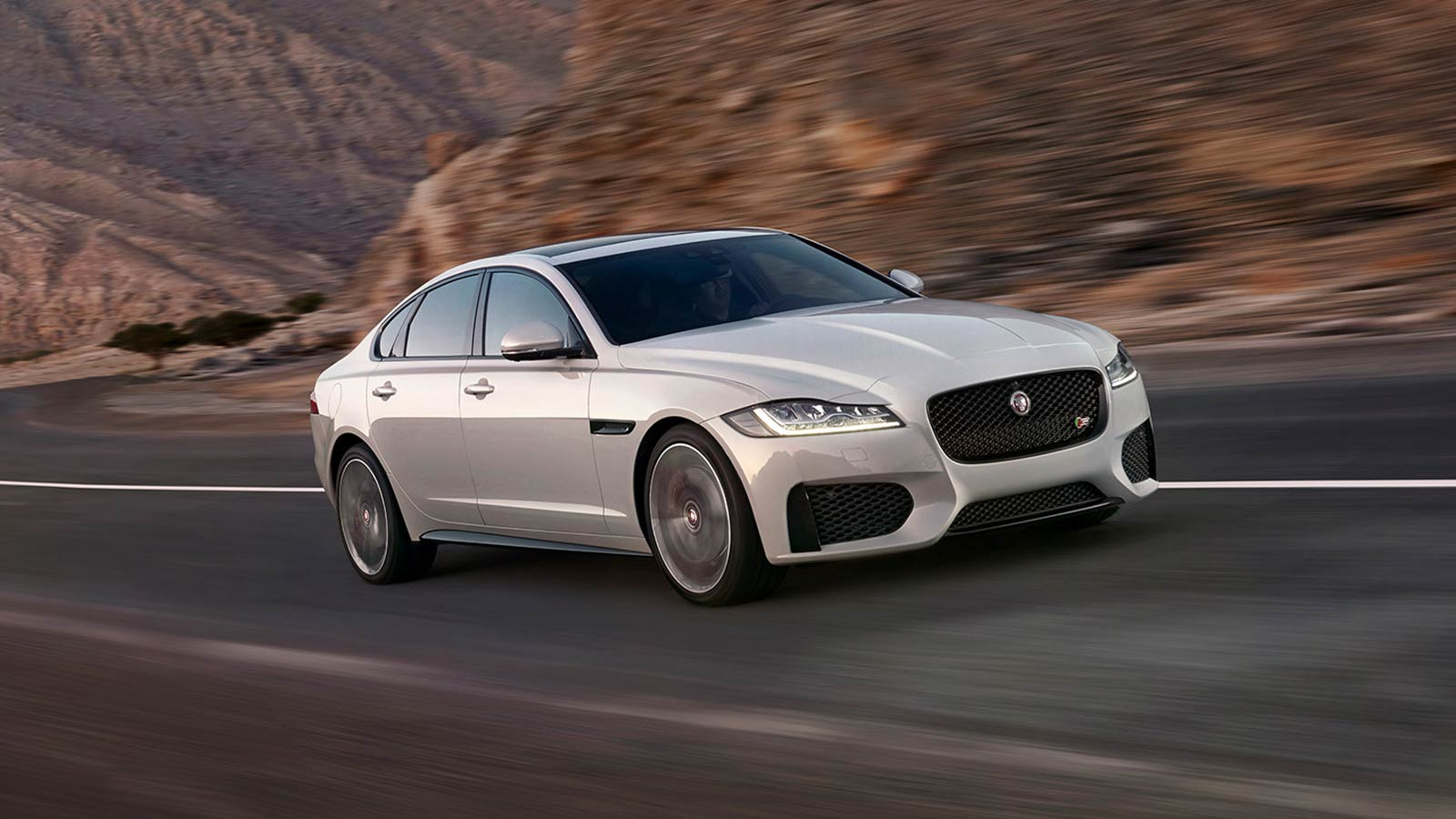 A White Jaguar XF Driving By Some Cliffs.