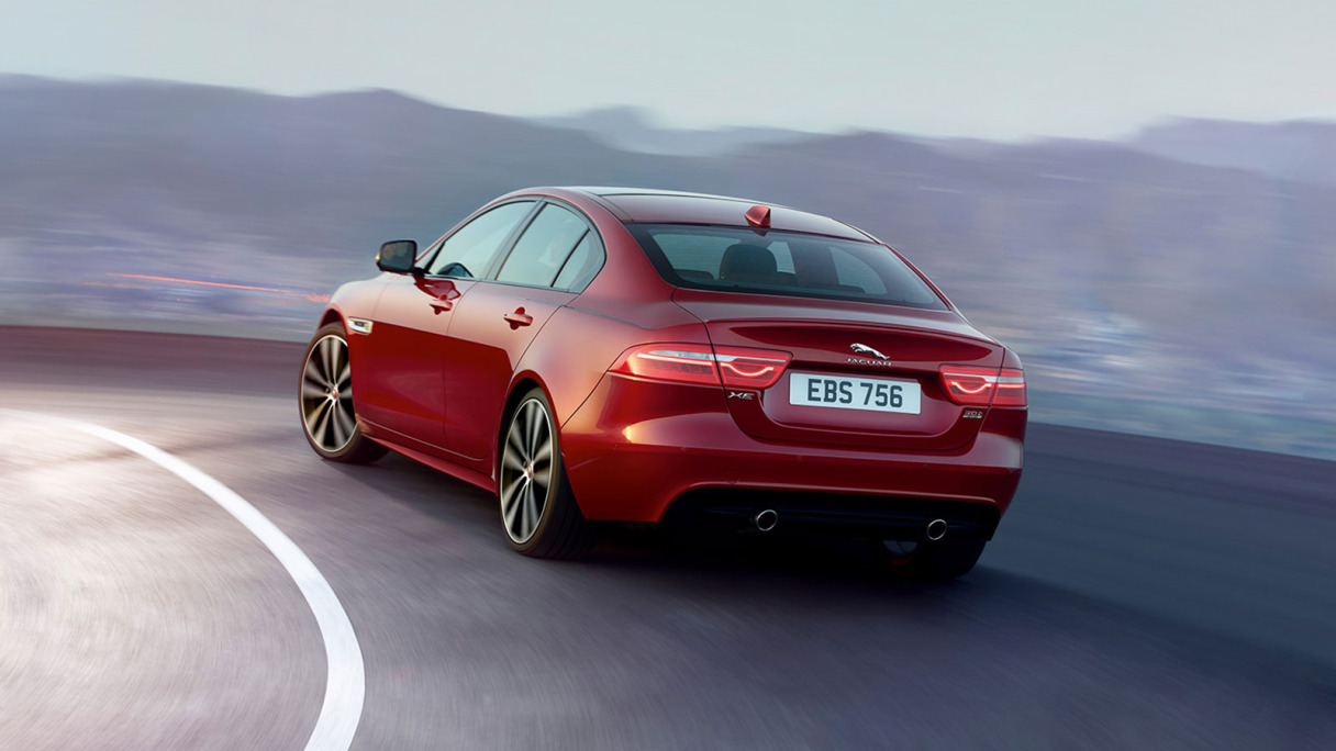 A Red Jaguar XE Driving Around A Bend.
