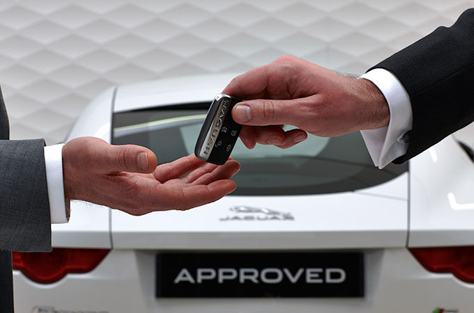 Two people handling keys to a Jaguar with a Jaguar in the background.