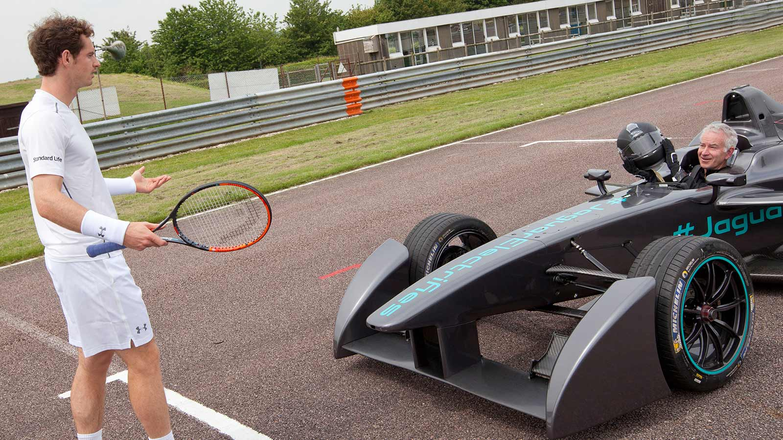 Andy Murray and racket in front of Jaguar Racing Car