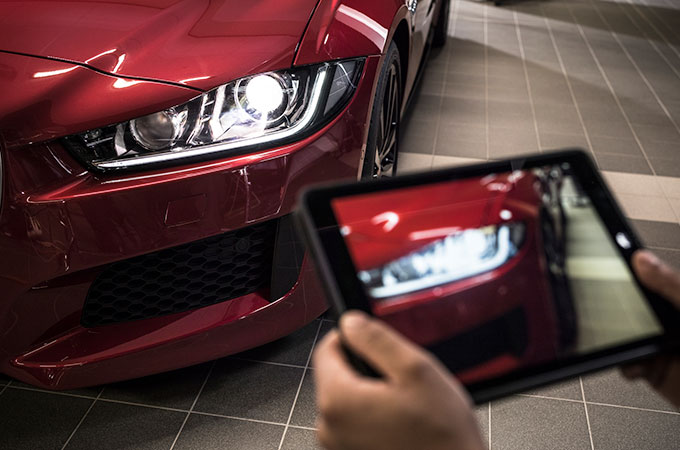 RECALL, shot of a tablet and a red Jaguar next to it.