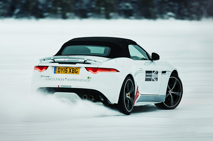 A White Jaguar Driving On Snow.