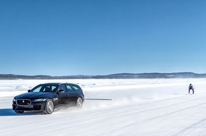 Jaguar XF driving in the ice, with someone skii-ing behind it.