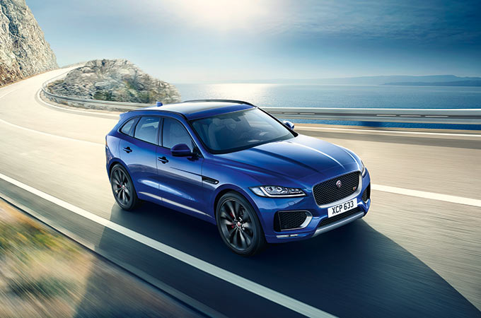 Blue Jaguar F-PACE driving on-road