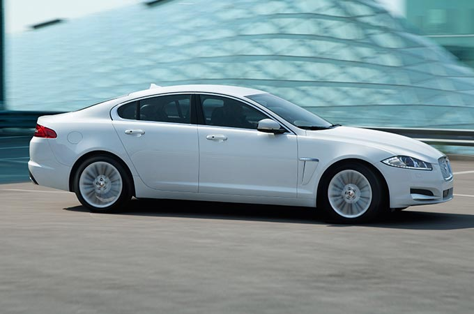 White XF Saloon parked next to side of building.