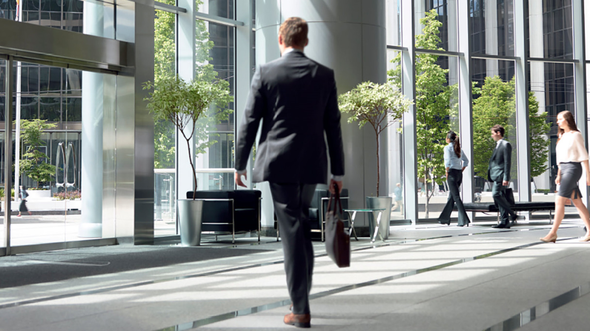 Office workers walk out of a modern building