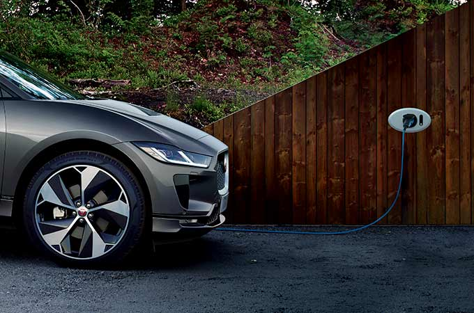 A grey Jaguar I-PACE charging from wall socket.