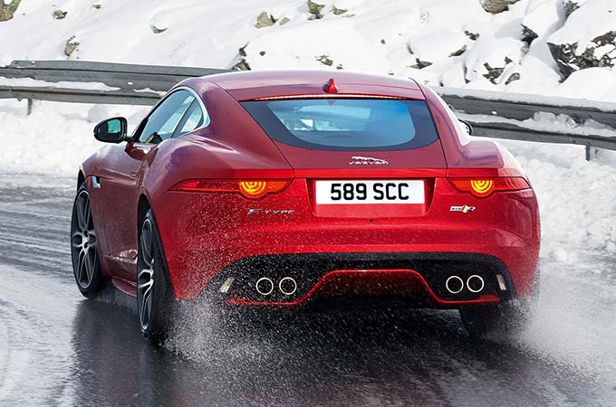 A Red Jaguar Driving On An Icy Road