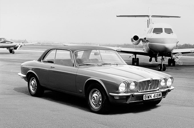 A Black And White Photo Of An Old Jaguar XJ Next To a Plane