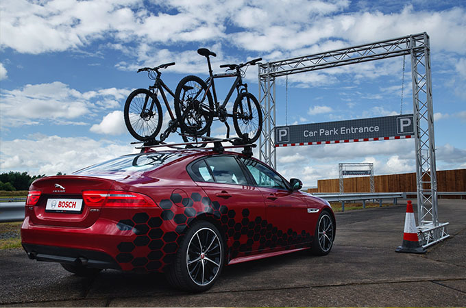 A Red Jaguar With Bicycles On The Roof