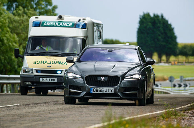 A Jaguar Driving Next To An Ambulance