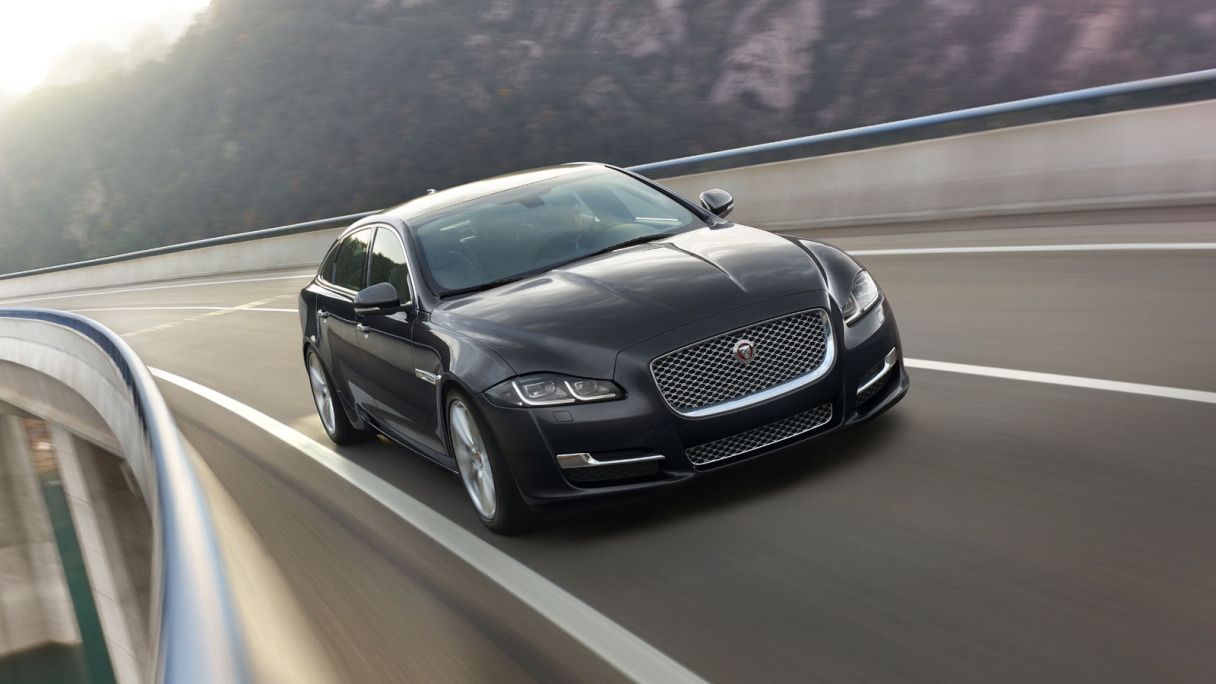 Black Jaguar XJ Driving Past A Mountain.