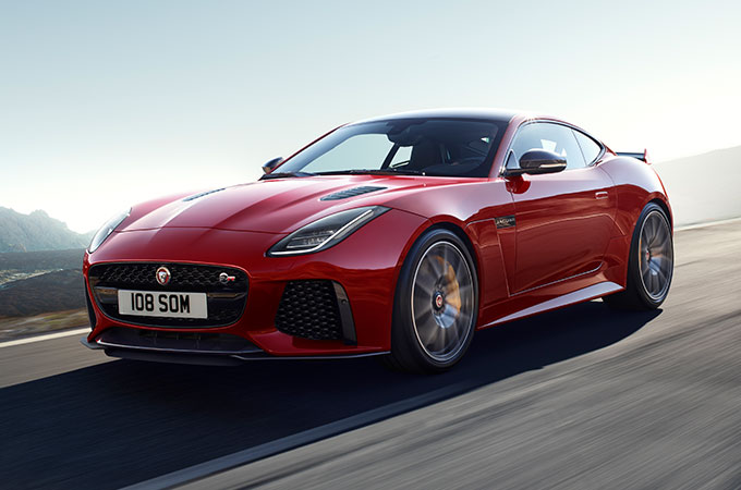 Red F-TYPE Coupé driving on road.
