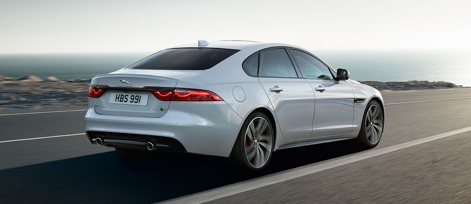 White XF Saloon driving on coastline.
