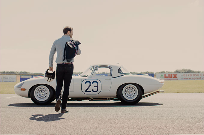 Man modelling in front of classic Jaguar racing vehicle.