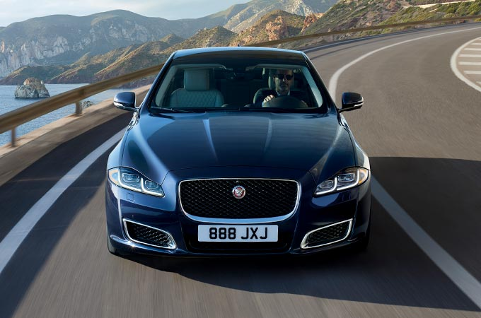 Jaguar XJ Driving On Bend Front View.