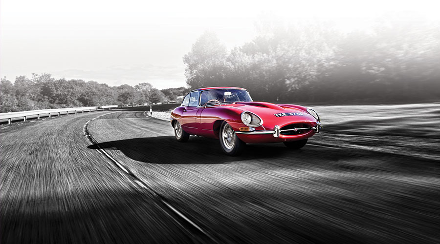 Red E-TYPE driving on racetrack.