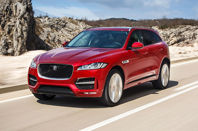 Red F-PACE driving in desert region.
