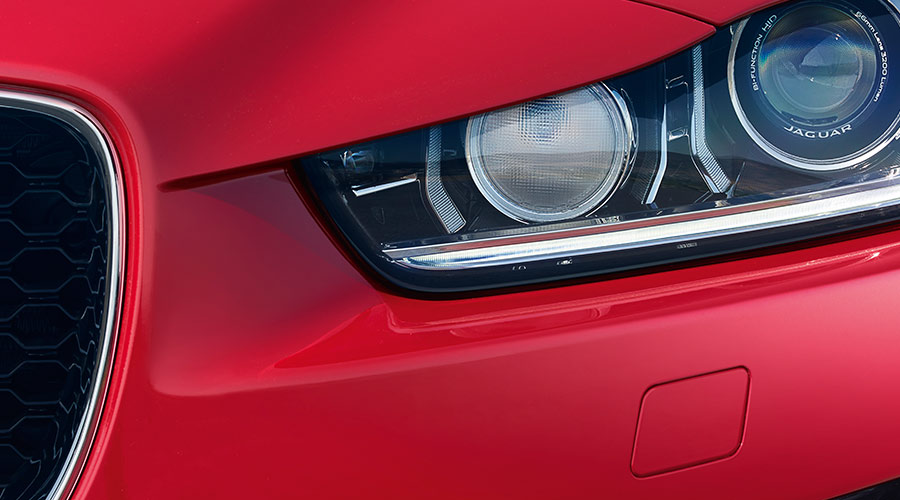 Close-up of red Jaguar's headlight.