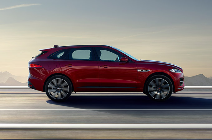 Side view of a red Jaguar F-PACE driving.