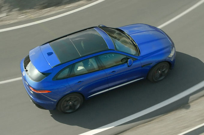 Blue F-PACE driving on road.