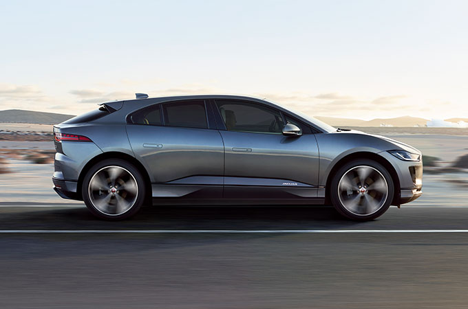 Side profile of I-PACE driving on road.