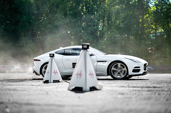 White Jaguar parked on a race track surrounded by orange traffic cones