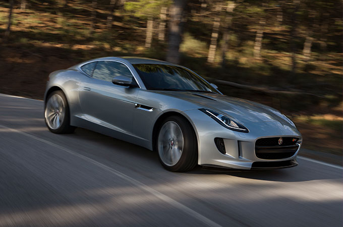 Silver Jaguar F-TYPE driving on country road.