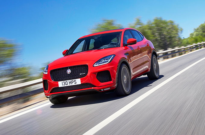 Red Jaguar E-PACE driving on country road.