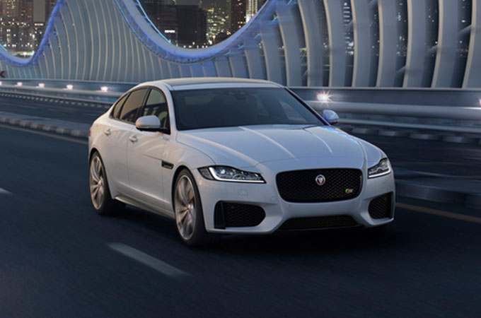White Jaguar XF driving in city environment.