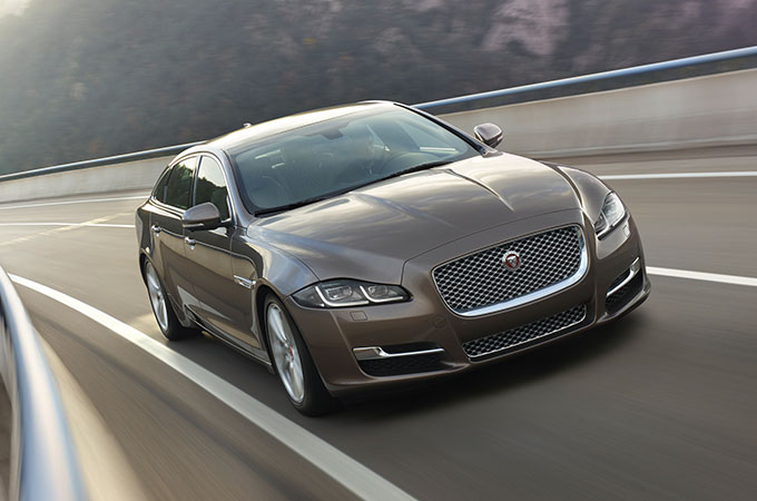 Grey Jaguar XJ driving on highway.