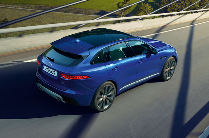 Blue F-PACE driving on highway.