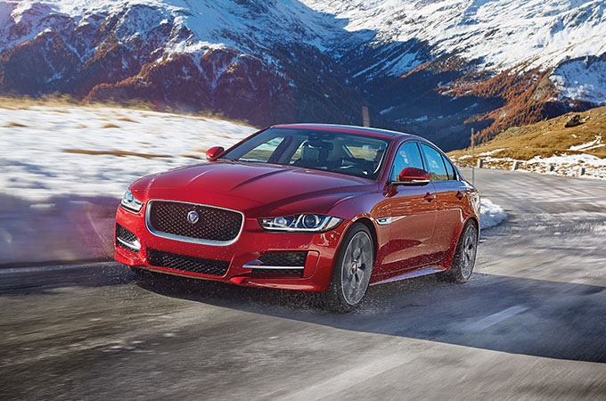 Jaguar Winter driving on a snowy mountain road.