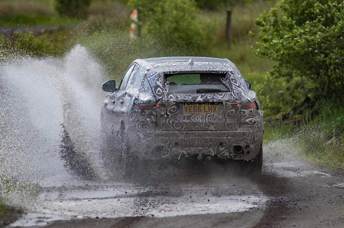 Black and white patterned E-Pace driving through mud track.